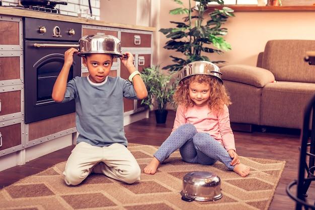 Nous voilà. fille émotive gardant la casserole sur sa tête tout en regardant directement la caméra