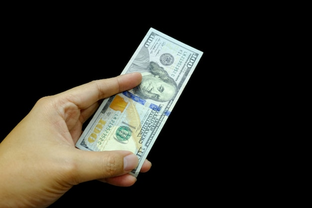 Nouveau billet de cent dollars en main isolé sur fond noir.