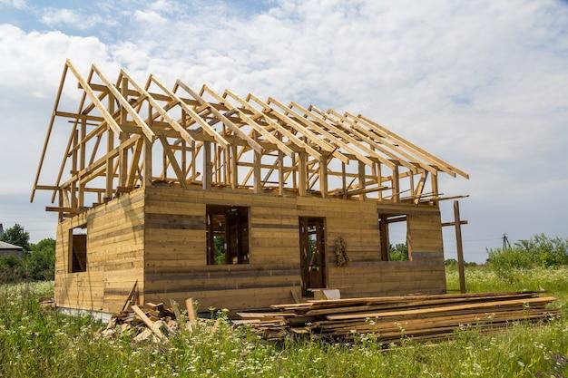 Nouveau chalet de matériaux de bois naturel écologique en construction dans un champ vert. murs en bois et charpente raide. propriété, investissement, construction professionnelle et concept de reconstruction.