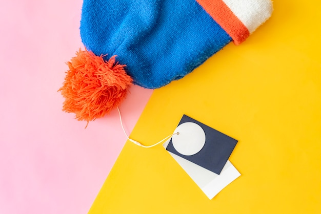 Nouveau chapeau de laine d'hiver chaud avec étiquette de prix copie espace concept créatif sur fond rose et jaune f