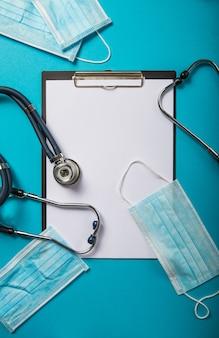 Nouveau concept de coronavirus 2019-ncov. masque respiratoire de protection médicale, stéthoscope sur fond bleu clair, vue de dessus.