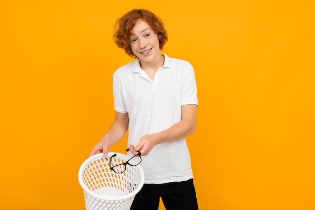 Nouveau concept de vision. adolescent dans un t-shirt blanc jette des lunettes dans une poubelle sur jaune avec copie espace