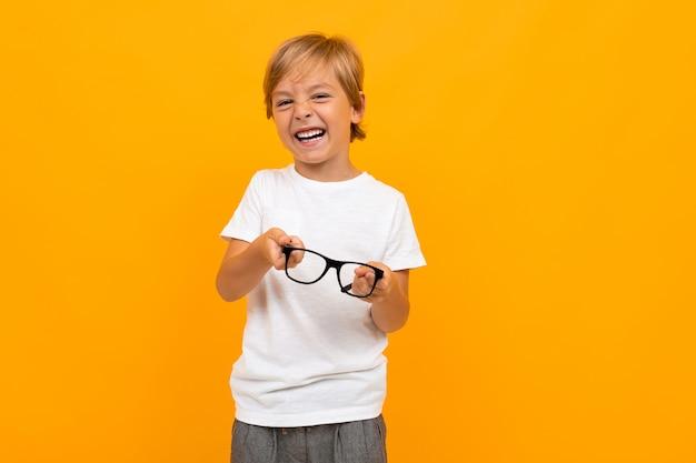 Nouveau concept de vision. garçon dans un t-shirt blanc louches tenant des lunettes dans ses mains sur un fond jaune