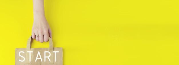 Nouveau Départ, Début, Concept D'entreprise. Sac à Provisions En Papier Brun Recyclé à La Main Avec L'icône Start De L'hologramme Sur Fond Jaune, Mise à Plat. Concept De Vente D'été. Concept De Service De Livraison Photo Premium