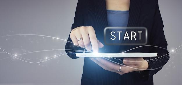 Nouveau départ, début, concept d'entreprise. tablette blanche dans la main d'une femme d'affaires avec signe de bouton start d'hologramme numérique sur fond gris.