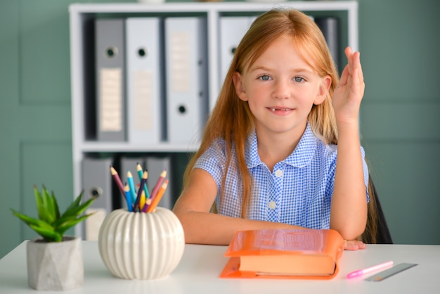 De nouveau à l'école, l'enfant travailleur est assis à une table à l'intérieur la fille lit un livre