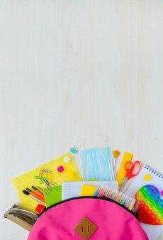 De nouveau à l'école fournitures scolaires colorées lumineuses dans le sac à dos pour l'école sur le fond en bois blanc