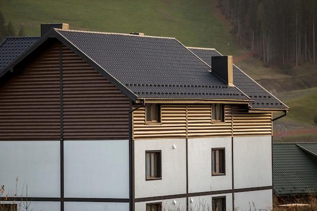 Nouveau joli chalet à deux étages blanc et brun avec toit en bardeaux dans une zone écologique sur bois brumeux et collines le jour d'été ensoleillé. propriété bien entretenue, concept immobilier.