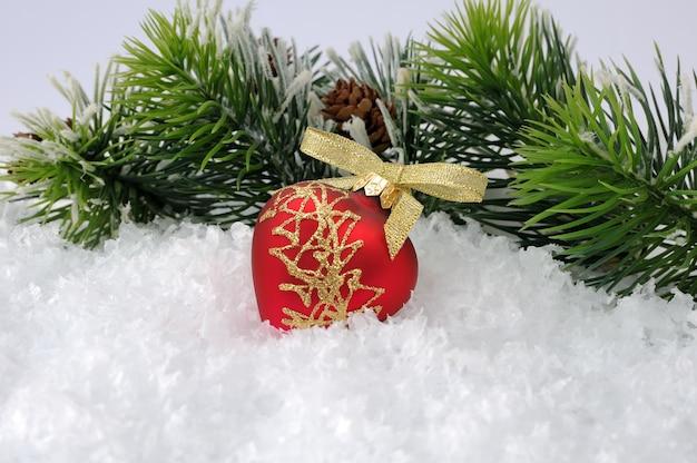 Nouveau jouet en forme de coeur dans la neige sur fond de branches de pin