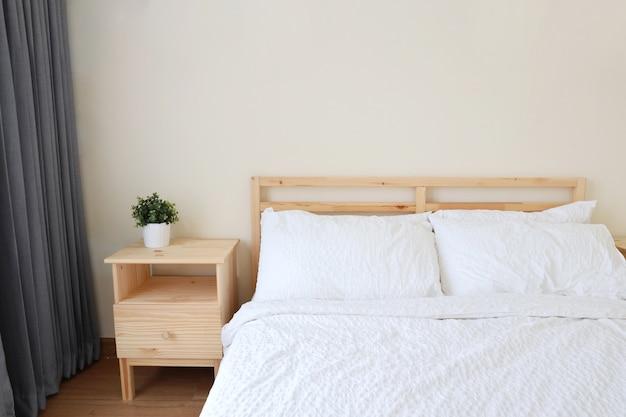 Nouveau lit blanc moderne dans la chambre à coucher avec lumière douce et claire
