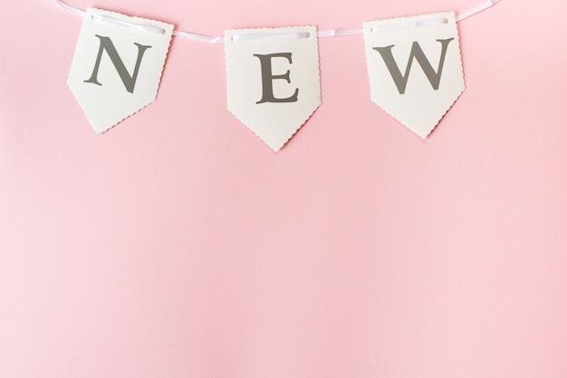 Nouveau mot sur fond rose pastel, vue de dessus avec espace de copie