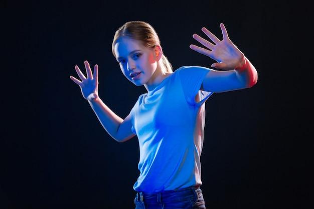 Nouveau multimédia. jolie jeune femme debout devant l'écran virtuel tout en le regardant
