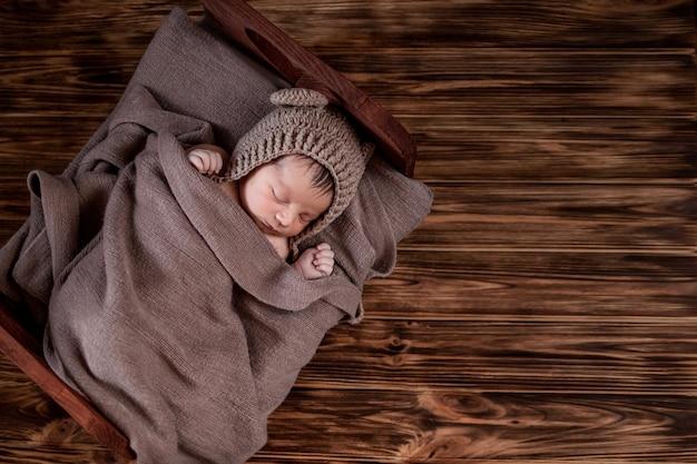 Nouveau-né, beau bébé se trouve dans une couverture de fourrure brune sur fond de bois