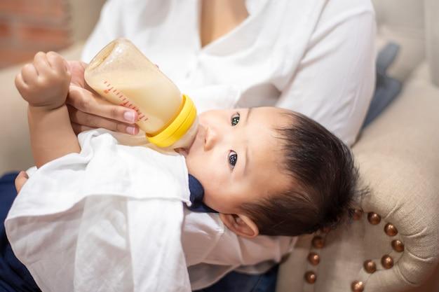 Nouveau-né bébé mignon boit du lait de bouteille par maman