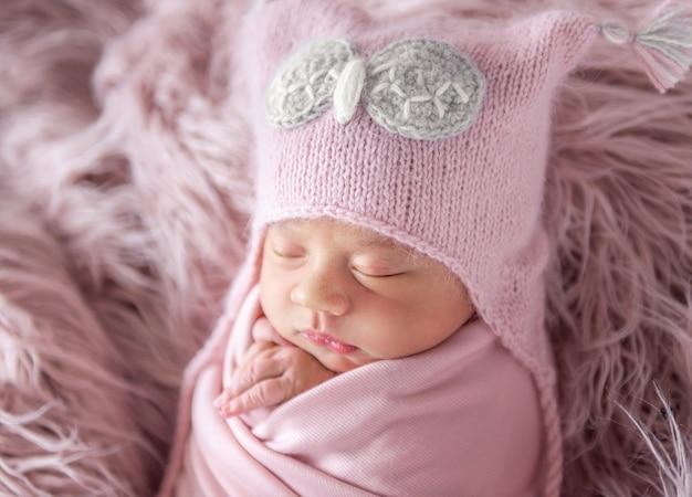 Nouveau-né en bonnet sur un tapis hirsute