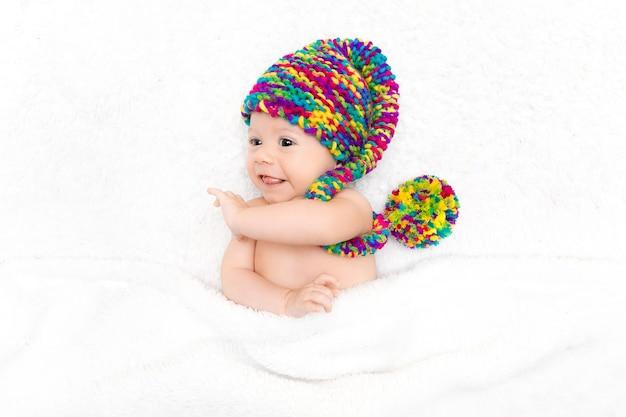 Nouveau-né couché sur une couverture blanche en grand chapeau tricoté drôle lumineux. concept d'adoption, parentalité heureuse