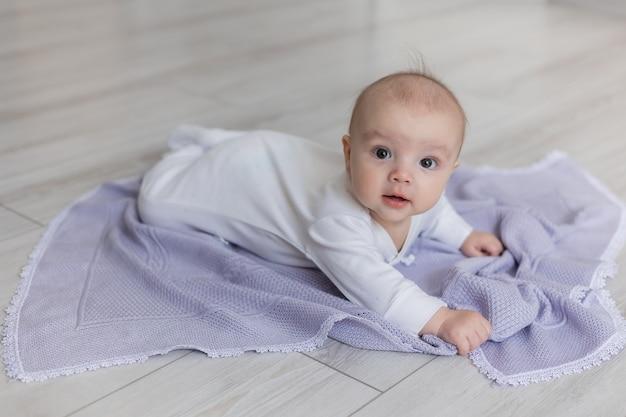 Nouveau-né dans un body blanc est allongé sur le ventre sur une couverture lilas tricotée sur le plancher en bois