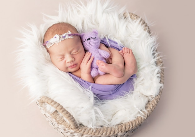 Nouveau-né dans un panier recouvert de laine avec jouet