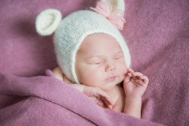 Un nouveau-né dort dans un chapeau avec des oreilles sur une couverture rose