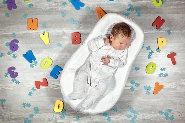 Le nouveau-né dort dans un matelas orthopédique spécial baby cocoon, sur un parquet en bois aux lettres multicolores tout autour. sommeil calme et sain chez les nouveau-nés.