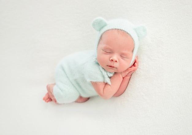 Nouveau-né dort dans des vêtements à la menthe