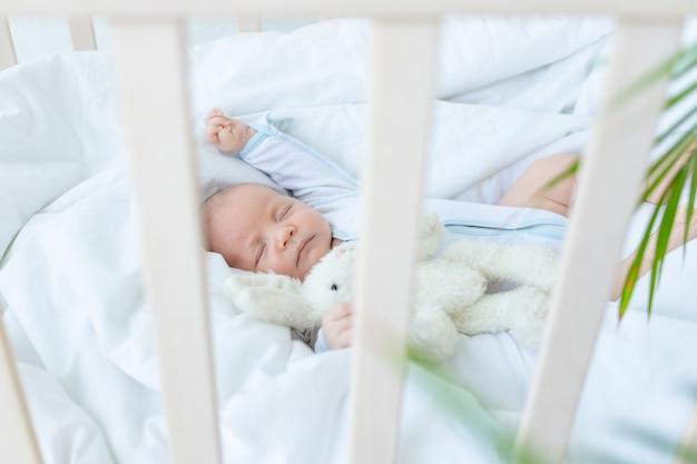 Le nouveau-né dort sept jours dans un berceau à la maison sur un lit en coton, vue sur le côté du berceau.