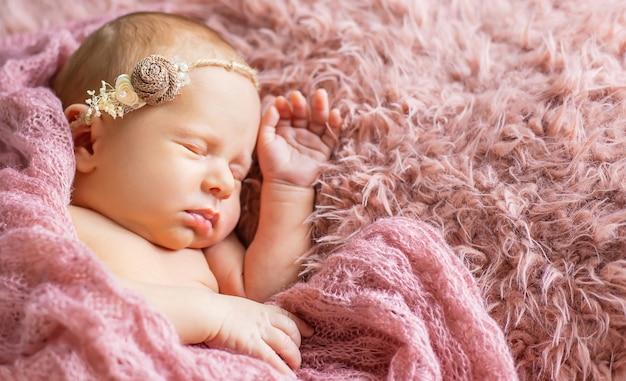 Nouveau-né endormi sur fond rose. mise au point sélective. gens.