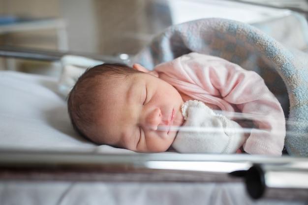 Un nouveau-né à l'hôpital repose dans la boîte. le petit bébé dort juste après la naissance.