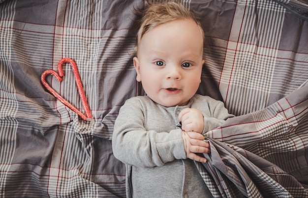 Nouveau-né jusqu'à quatre mois allongé sur un lit gris, à côté d'un coeur rouge