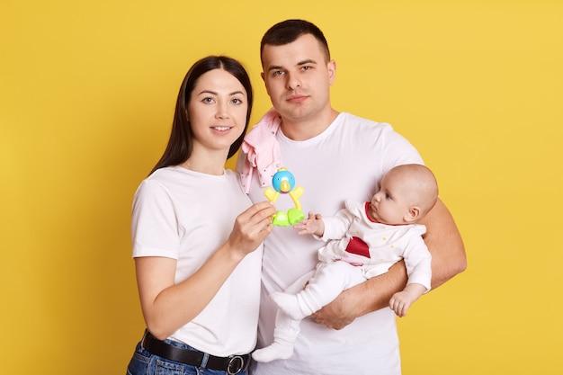 Nouveau-né et parents portant un fond jaune, famille portant des t-shirts blancs, regardant la caméra, mère montrant un pouf à l'enfant, famille heureuse, passer du temps ensemble.