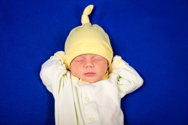 Nouveau-né petit garçon dormant sur une couverture bleue. emballage d'articles pour bébé