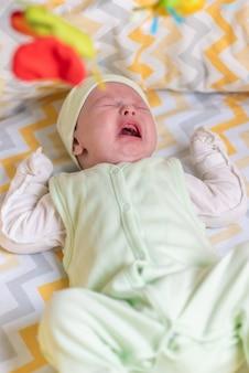 Un nouveau-né pleure dans le berceau à cause des coliques