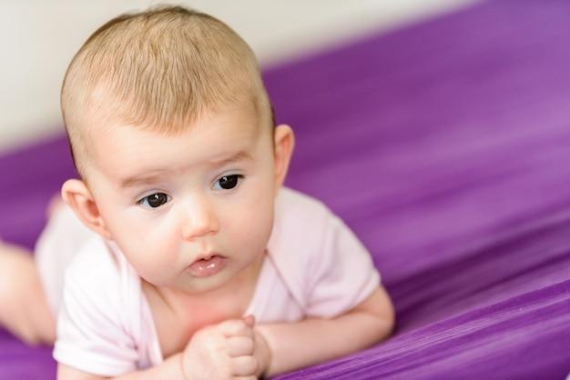 Nouveau-né avec un visage adorable, calme et détendu allongé sur son lit