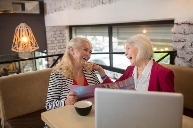 Nouveau projet. deux dames âgées blondes assises devant l'ordinateur portable et ayant l'air impliquées