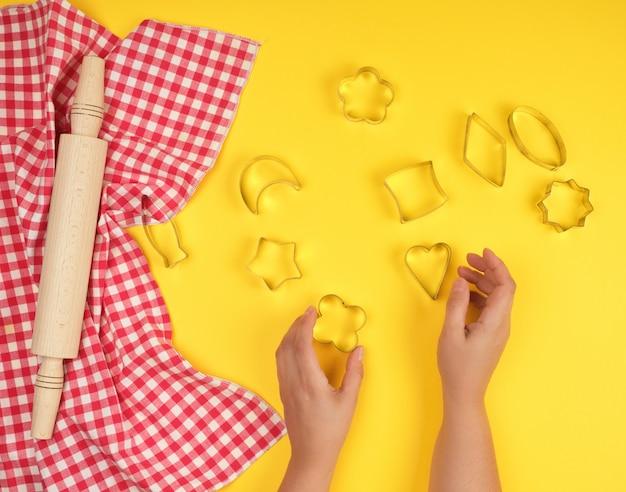 Nouveau rouleau à pâtisserie en bois sur une serviette en tissu rouge et deux mains féminines