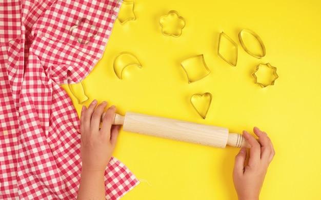 Nouveau rouleau à pâtisserie en bois, serviette en tissu rouge et deux mains féminines
