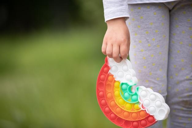Nouveau silicone populaire un jouet antistress coloré arc-en-ciel pop-le dans les mains d'un enfant