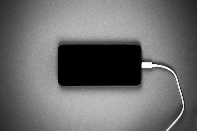 Nouveau smartphone avec un écran noir avec un fil blanc du chargeur