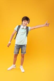 Nouveau style de vie. beau garçon exubérant portant un cartable et tenant son pouce vers le haut