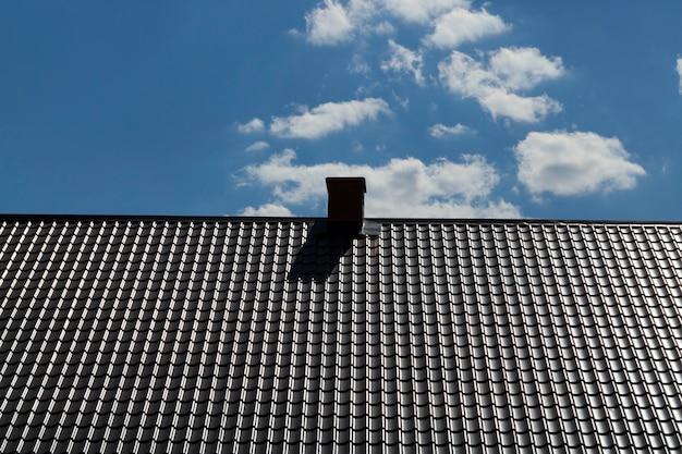Nouveau toit métallique avec cheminée sur fond de ciel bleu,