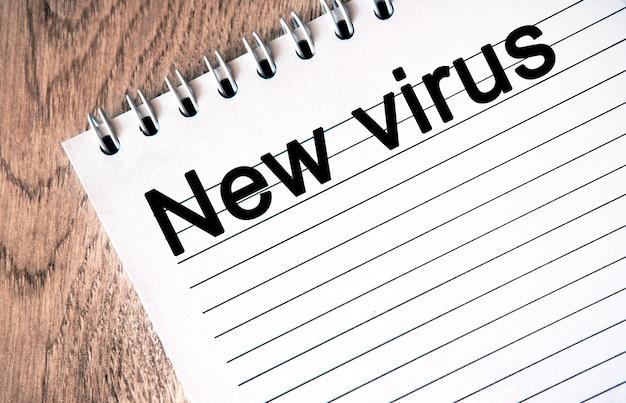 Nouveau virus - texte sur un cahier blanc, fond en bois