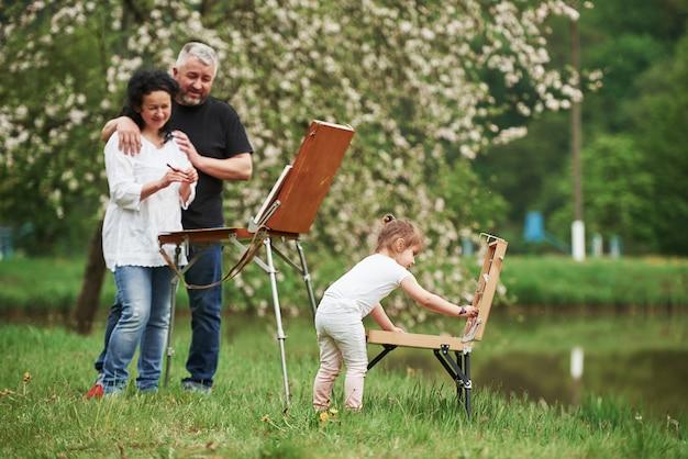 De nouveaux départs. grand-mère et grand-père s'amusent à l'extérieur avec leur petite-fille. conception de peinture