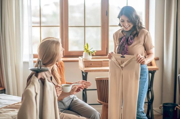 Nouveaux habits. femme brune montrant ses nouveaux achats à ses amis