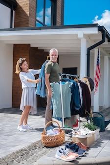 Nouveaux habits. homme d'affaires aux cheveux gris barbu venant à la vente de garage avec sa femme élégante et attrayante tout en achetant de nouveaux vêtements