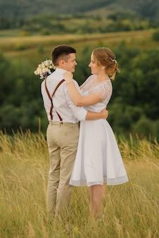 Les nouveaux mariés amoureux s'embrassent et se regardent contre la belle nature verte