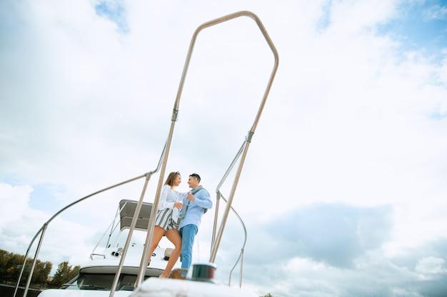 Les nouveaux mariés amoureux sur un voilier avec du champagne - concept de mode de vie alternatif exclusif heureux. couple, célébrer, champagne, bateau, avoir, fête, petite amie, vacances