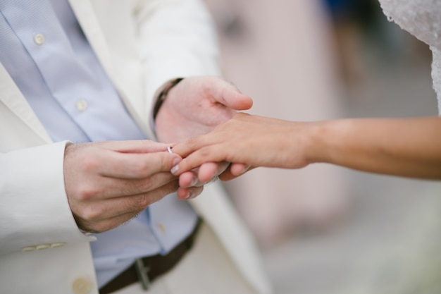 Les nouveaux mariés échangent des anneaux, le marié met l'anneau sur la main de la mariée