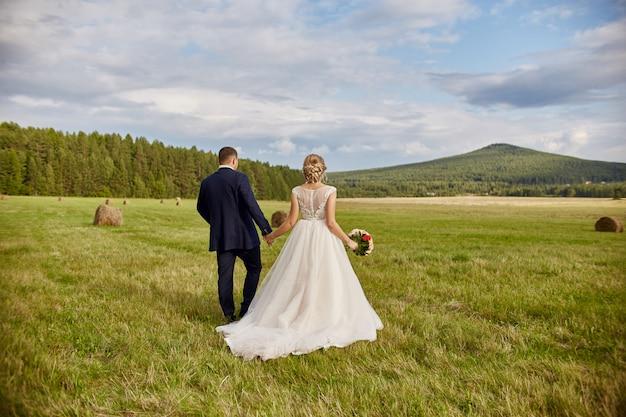 Les nouveaux mariés marchent et se détendent dans le champ