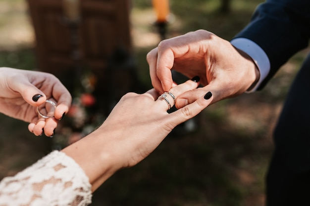 Les nouveaux mariés mettent des bagues, échangent des bagues, des alliances, une cérémonie de mariage, un couple, un jeune couple, l'amour, des bagues.
