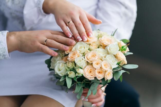 Les nouveaux mariés montrent leurs mains avec des anneaux de mariage